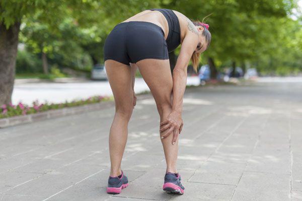 Девушка держится за растянутую икроножную мышцу