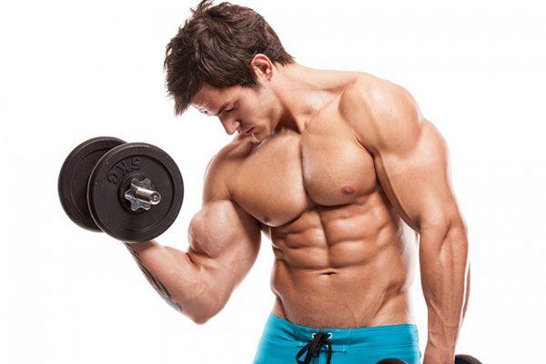 Мускулистый мужчина выполняет подъем гантели на бицепс.