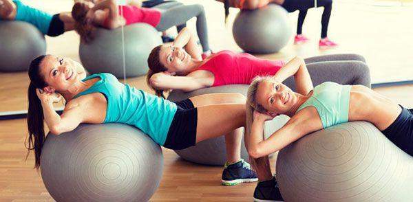 Девушки выполняют упражнения на фитболе
