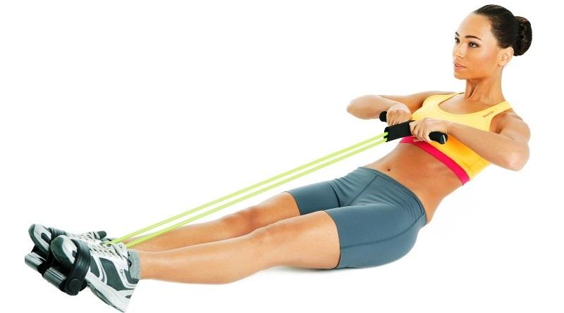 девушка выполняет упражнение с эспандером