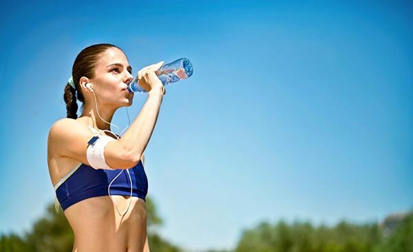 Девушка пьёт воду на пробежке