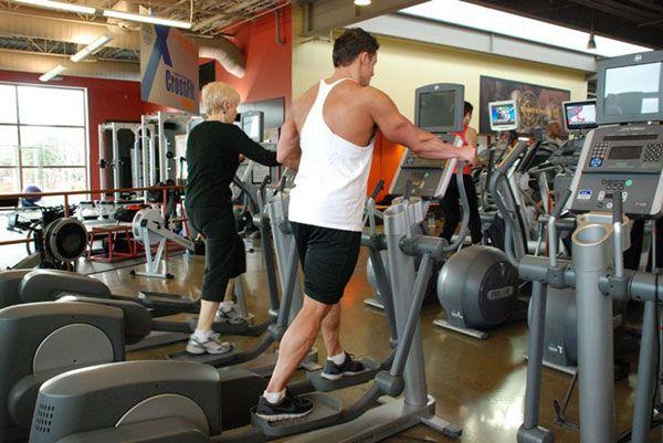 Выполнение упражнений на эллипсоиде в спортивном зале.