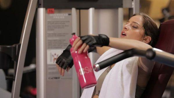 Девушка пьет после тренировки